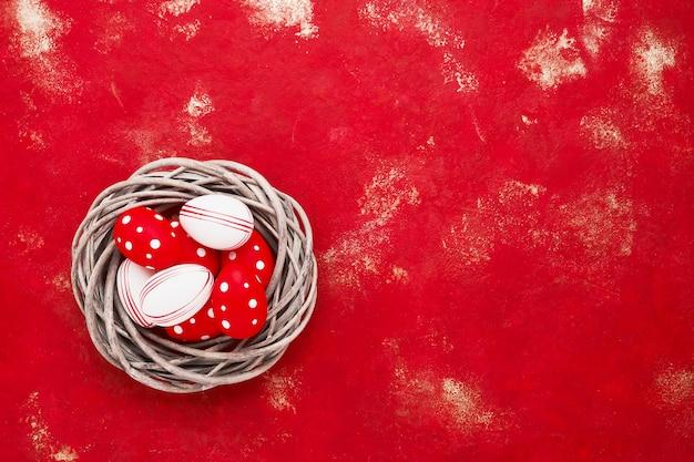 Uova di pasqua decorative in un nido su uno sfondo rosso.