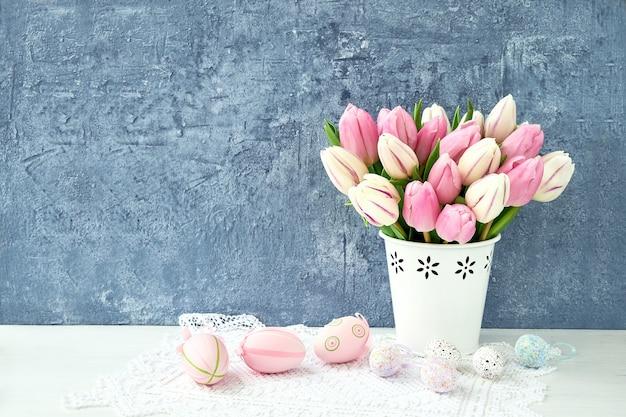Uova di pasqua decorative e tulipani rosa in vaso. copia spazio