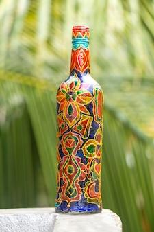 La bottiglia di vetro decorativa è dipinta e decorata con strass