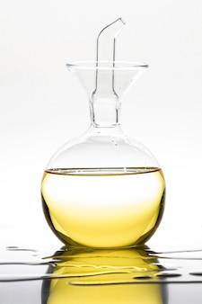 Bottiglia di vetro decorativa con olio d'oliva su bianco.