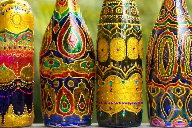 Le bottiglie di vetro decorative sono dipinte e decorate con strass