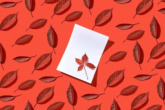Biglietto di auguri decorativo con caduta rossa lascia un foglio di carta bianco