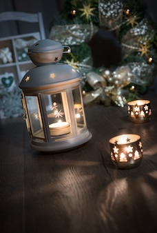 Lanterne decorative, candele e decorazioni di natale su legno, spazio del testo.