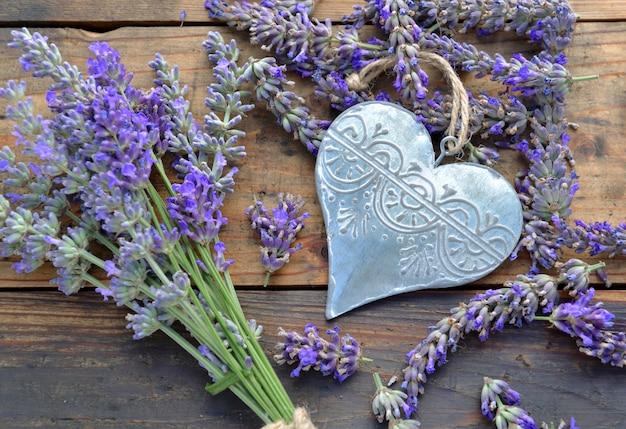 Cuore decorativo del metallo fra i fiori di lavanda su fondo di legno
