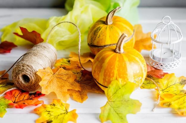 Mini zucche decorative con foglie secche cadono, candela su sfondo scuro,