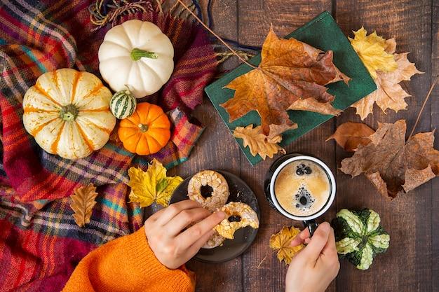 Zucche, mani del fogliame e caffè decorativi con i biscotti sulla tavola di legno