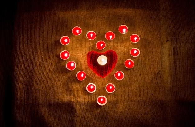 Candele rosse decorative che formano la forma del cuore su un panno di lino