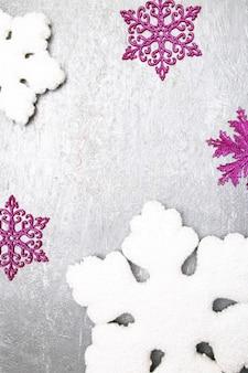 Fiocco di neve decorativo bianco e rosa su sfondo grigio