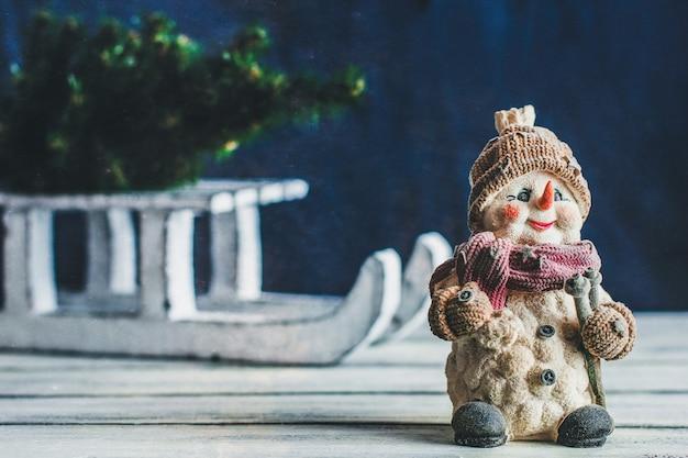 Pupazzo di neve decorativo sullo sfondo delle slitte invernali