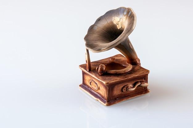 La statuetta decorativa del grammofono su sfondo bianco. foto ravvicinata