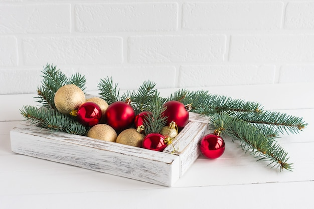 Scatola bianca decorativa in legno con palle di natale festive su un tavolo di legno bianco su un muro di mattoni bianchi e rami di abete rosso.
