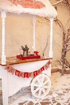 Carrello in legno bianco decorativo con caramelle natalizie.