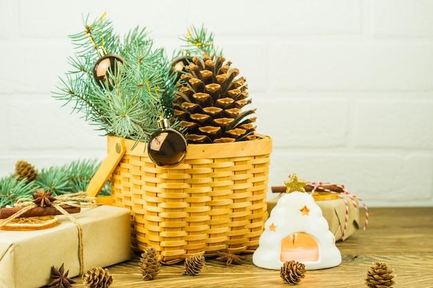 Cesto decorativo in vimini con rami di abete verde, palline e cono di cedro. scatole regalo e una candela in un candeliere su un tavolo di legno.