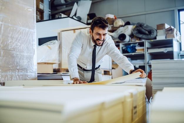 Ingegnere grafico barbuto laborioso dedicato in merda e cravatta in piedi in magazzino e prendere fogli