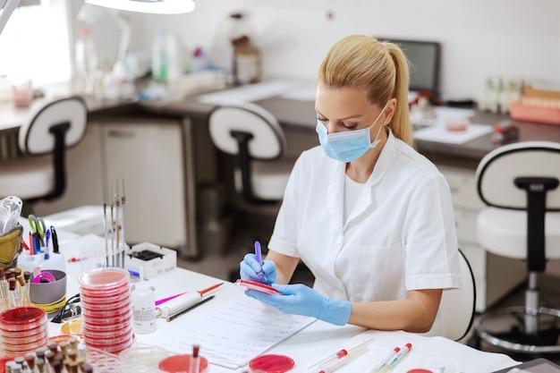 Assistente di laboratorio dedicato con maschera protettiva e guanti per scrivere sui risultati dei test delle capsule di petri.