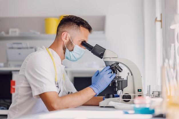 Assistente di laboratorio maschile dedicato con guanti di gomma e maschera facciale utilizzando il microscopio durante il coronavirus.