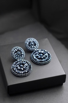 Orecchini ricamati di perline blu intenso sulla superficie nera Foto Premium