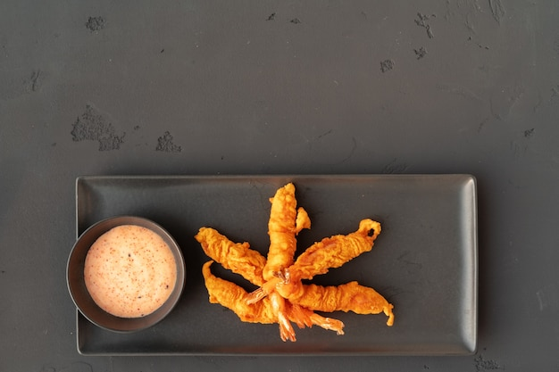 Gamberi croccanti fritti nel grasso bollente con salsa sulla vista superiore del piatto di ceramica nera