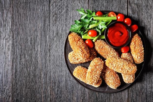 Crocchette di riso fritte suppli al telefono ripiene di mozzarella servite su un piatto nero con gambi di sedano, pomodori e ketchup su un tavolo di legno scuro, vista dall'alto, spazio copia