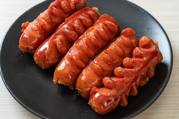 Spiedino di salsiccia fritta su piastra nera