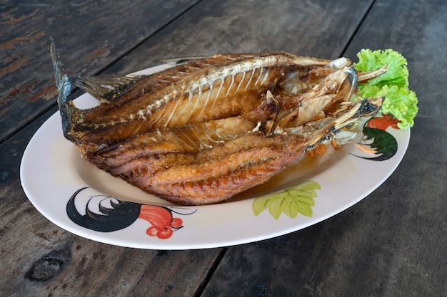 Pesce di branzino fritto nel grasso bollente sulla tavola di legno, menu tailandese dei frutti di mare
