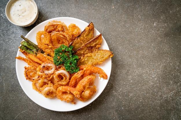 Frutti di mare fritti (gamberetti e calamari) con verdure miste - stile di cibo malsano