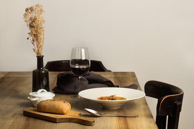 Un piatto profondo di lenticchie stufato con un bicchiere di vino su un tavolo di legno