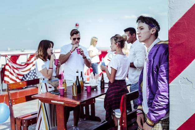 Nel profondo dei pensieri. gruppo di giovani che celebrano la festa di stato e testano le bevande alcoliche