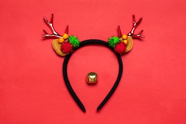 Muso di cervo realizzato con orlo con corna di cervo e orecchie, campana di natale dorata isolata su sfondo rosso