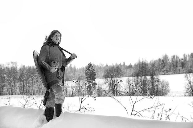 Difensore il giovane guerriero in armatura di maglia armato di spada e ascia