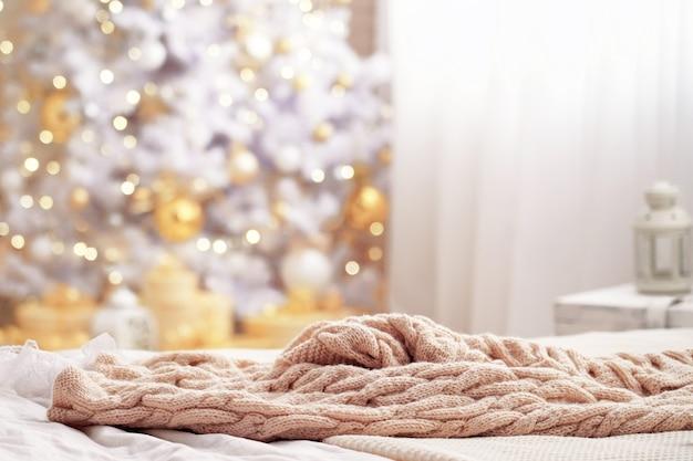 Sfondo sfocato con luce natalizia sfocata. il bokeh magico del nuovo anno si accende con colori caldi. coperta lavorata a maglia sul letto.