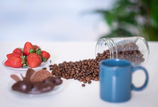 Tazza di caffè blu sfocato e chicchi di caffè sul tavolo bianco fragole rosse e cioccolato