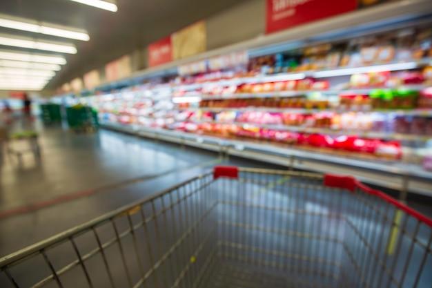 La sfocatura sfocata del supermercato che acquista la carne del carrello con prodotti lattiero-caseari.