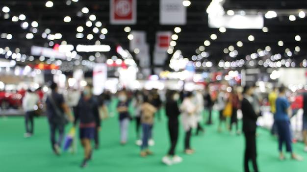 Folla sfocata sfocata persone anonime che camminano alla fiera fieristica in occasione di eventi congressuali o sala conferenze. sfondo chiaro bokeh.
