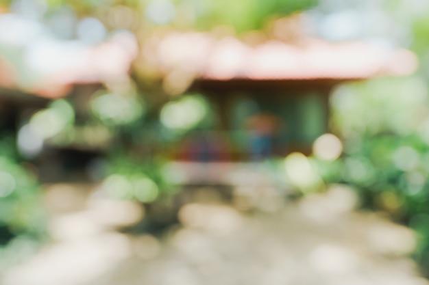 Bokeh sfocato e sfocatura dello sfondo di alberi da giardino alla luce del sole.