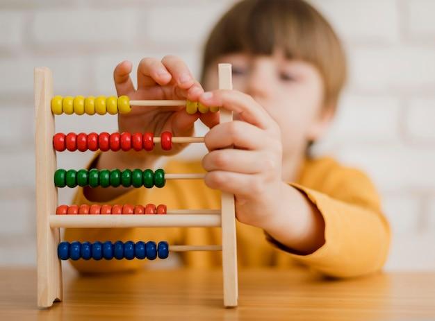 Bambino sfocato che impara a contare usando l'abaco