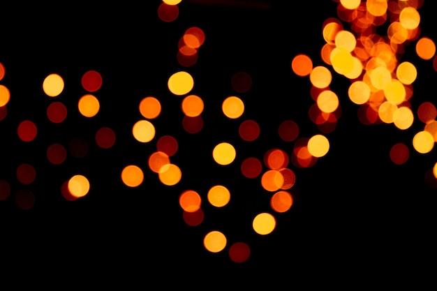 Fondo dell'estratto del bokeh di notte dell'oro della città defocused. sfocato molte luci gialle rotonde su sfondo scuro.