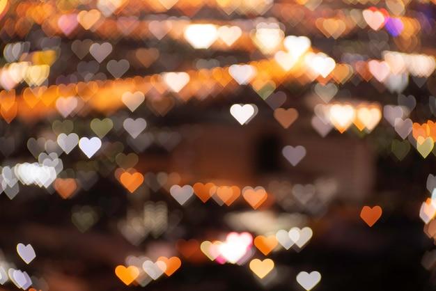 Sfocato bokeh sfocato luci arancioni e dorate a forma di cuore. sfondo nero festivo di natale o capodanno e san valentino.