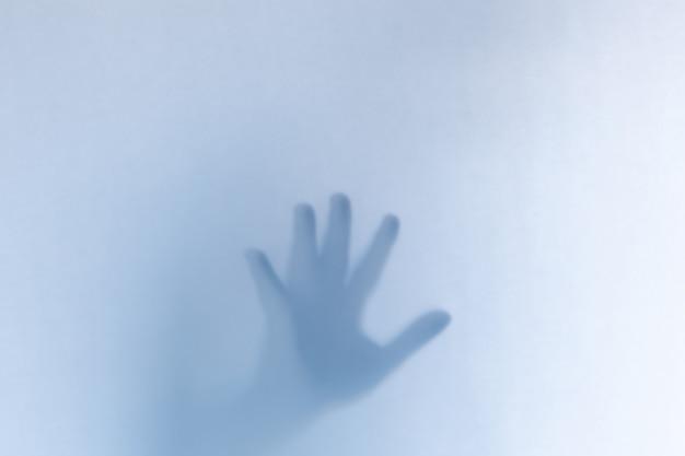 Mani fantasma spaventose defocused dietro un vetro bianco