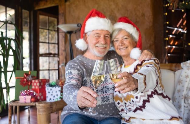 Coppia senior sfocata in cappelli di babbo natale che si abbraccia a casa nel periodo natalizio brindando con bicchieri di vino. seduto all'interno di un rustico chalet di montagna con albero di natale, regali e luci sullo sfondo