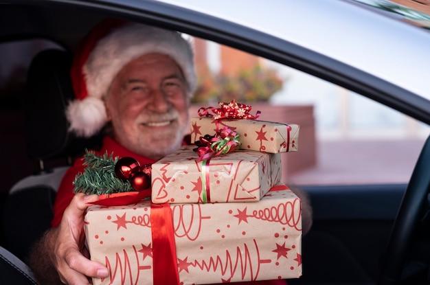 Defocused uomo anziano sorridente dentro la sua auto che indossa un cappello da babbo natale pronto per la consegna a domicilio dei regali di natale. un vecchio nonno barbuto