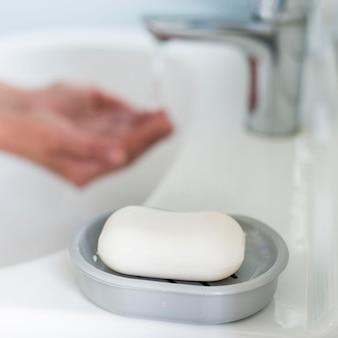Sfocato lavando le mani nel lavandino con una saponetta