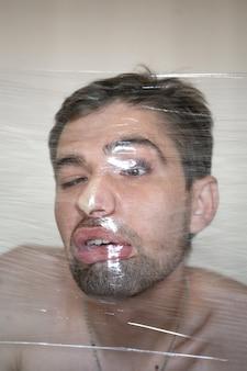 Volto deformato. un ritratto distorto di un uomo attraverso un nastro di plastica.