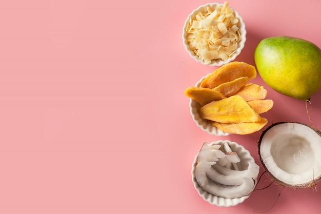 Chip disidratati e secchi del cocco e del mango in ciotola bianca sul rosa. avvicinamento.
