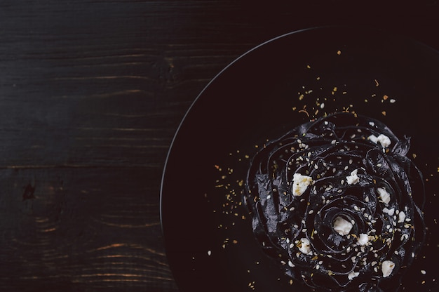 Pasta fatta in casa nera delicata con formaggio feta ed erbe provenzali su un piatto nero