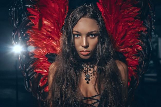 Bella donna delicata del brunette che propone con le ali rosse scure di angelo. colpo dello studio