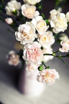 Delicato bouquet di garofani in vaso vintage.
