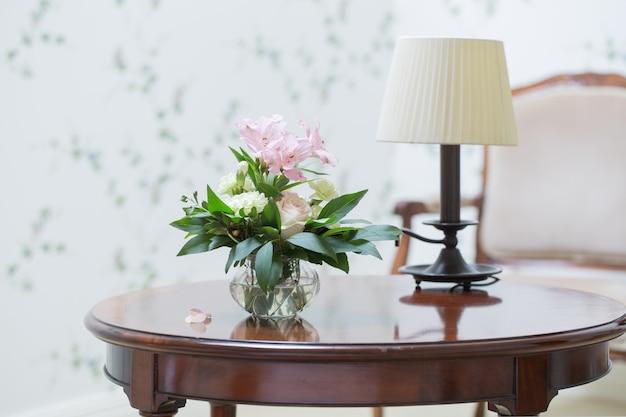 Bouquet delicato in vaso di vetro in interni vintage