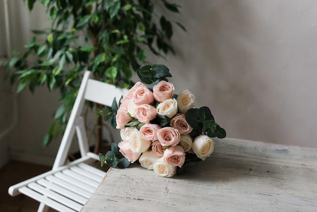 Sul tavolo giace un delicato bouquet di rose. bellissimo mazzo di rose su un tavolo di legno.