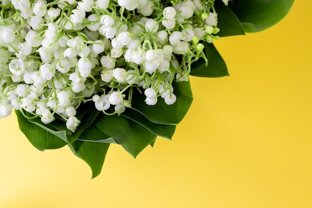 Delicato bouquet di mughetti bianchi in foglie verdi su fondo giallo brillante con spazio copia. messa a fuoco selettiva. vista del primo piano